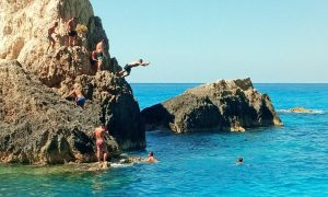 People jumping in the sea from a rock in Navagio Beach