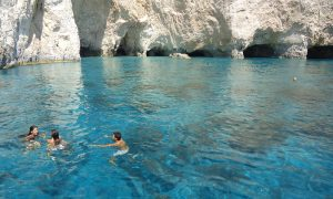 People swimming in blue waters in Zakynthos