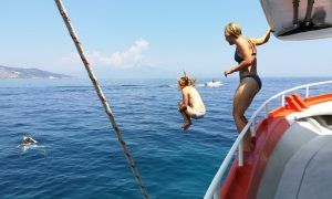 People jumping into the water from our traditional fishing boat in Zakynthos